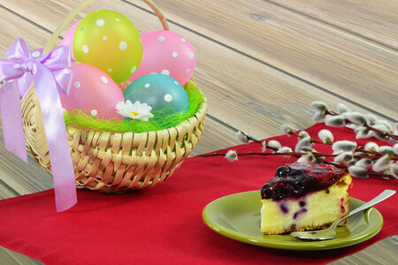 Basket of Easter eggs, piece of cake and pussy willow on wooden table. photo