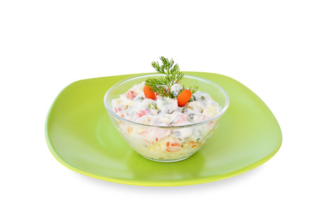 Russian traditional salad olivier in glass bowl, isolated. photo