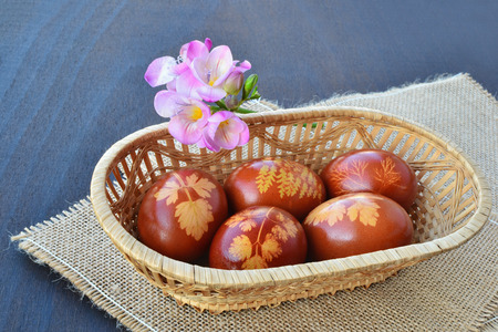Beautiful Easter eggs dyed with onion skin in small basket.