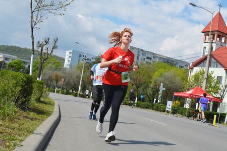 forground: Cluj-Napoca, Romania - April 13, 2014: Unidentified marathon runners, young woman in the forground running on the streets of Cluj-Napoca at the AROBS International Marathon. Editorial