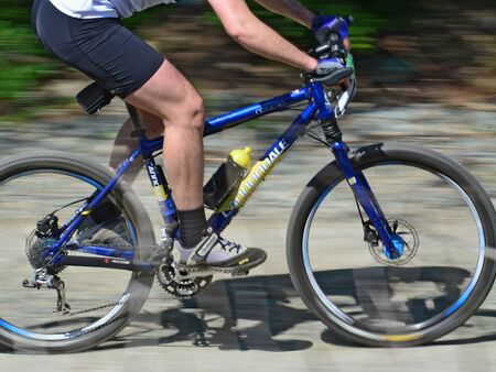CLUJ-NAPOCA, ROMANIA - APRIL 27, 2014:  Bike and legs of an unidentified male athlete at Cluj Bike Challenge. - motion blur.
