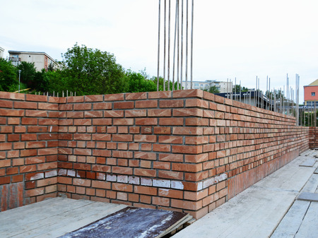 Red brick masonry on house under construction. Фото со стока