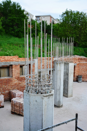 Reinforced concrete pillars and red brick masonry on house under construction.