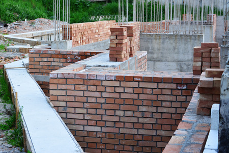reinforced: Retaining wall, red brick masonry and reinforced concrete pillars on house under construction.