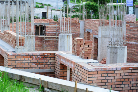 Red brick masonry and reinforced concrete pillars on house under construction. Stockfoto