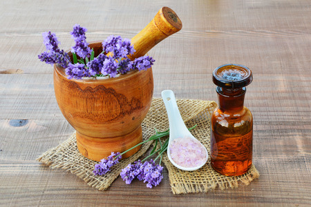 Essential lavender oil, wooden mortar with fresh lavender flowers, bath salts on wooden .