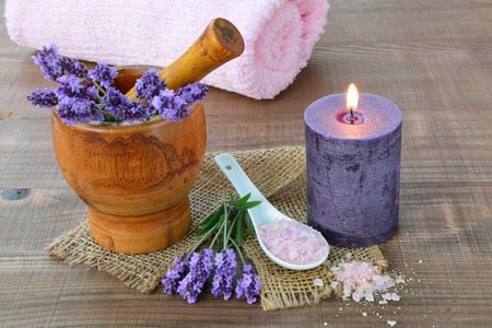 perfumed candle: Fresh lavender in wooden mortar, bath salts and towel, candle. Stock Photo