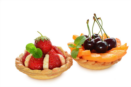 Tasty tartlets with fresh fruits isolated on white background. photo