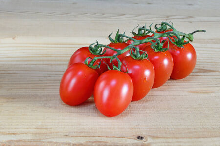 Cherry tomatoes on the vine over wooden table  photo