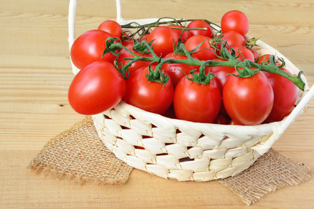 oblong: Cherry tomatoes in a basket over wooden background