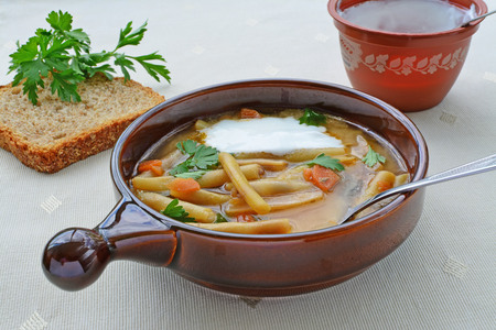 Yellow wax bean soup with vegetables, sour cream and green parsley  photo