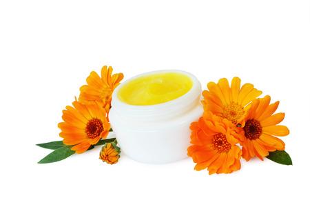 cremas faciales: Piel crema hidratante en el tarro blanco con flores aisladas.