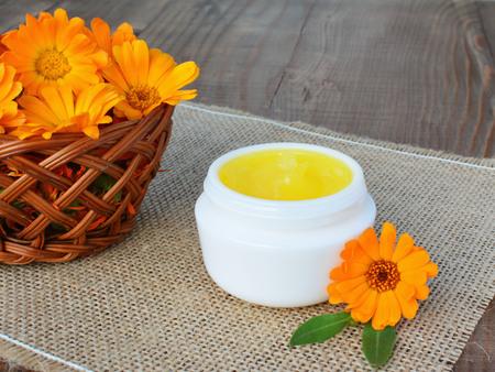 cremas faciales: Cal�ndula pomada con flores de cal�ndula frescas. Foto de archivo