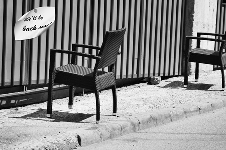 the back gate: Two chairs on the sidewalk in front of a rolling gate. A note indicates that employers are having a break but theyll be back soon.