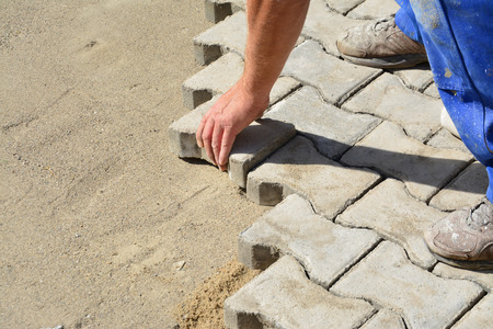 Worker laying pavers onto the bedding sand and fitting them into place. photo