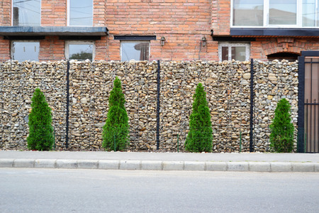 Gabion wire mesh fencing with natural stones and support posts. photo
