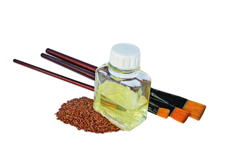 Linseed oil painting medium in a bottle, flax seeds and paintbrushes isolated on white.