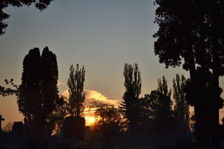 tumbas: Cementerio en Rumania al atardecer con siluetas de �rboles y tumbas. Foto de archivo