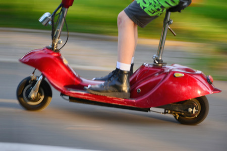Young boy riding a vintage electric scooter in the park.