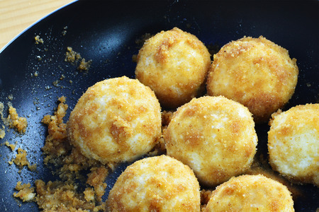 Cottage cheese dumplings with breadcrumbs in frying pan.