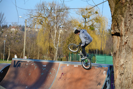 bmx bike: CLUJ-NAPOCA, ROMANIA - March 16, 2015: Unidentified young man jumps with his BMX bike on a ramp in skate park. Editorial