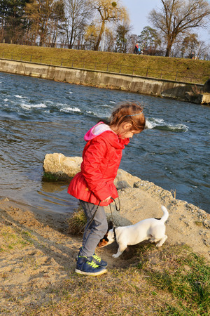 CLUJ-NAPOCA, ROMANIA - March 16, 2015: Unidentified young girl plays with her dog at the river. The Somesul-Mic river banks is the favorite hang out place in the city for dogs and their owners.