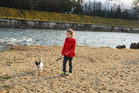 tricoloured: CLUJ-NAPOCA, ROMANIA - March 16, 2015: Unidentified young girl walks her dog at the river. The Somesul-Mic river banks is the favorite hangout place in the city for dogs and their owners.