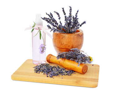 Lavender flowers in mortar, hydrosol bottle on wooden board isolated on white background. Banque d'images