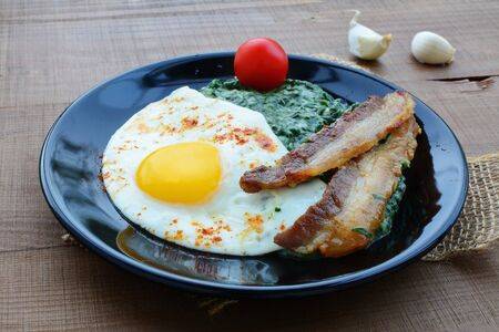 creamed: Creamed spinach with fried egg and bacon. Wholesome homemade breakfast on rustic wooden table.