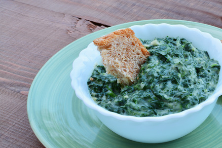 Homemade creamed spinach in a white bowl. Fresh creamy spinach dip on rustic wooden table.