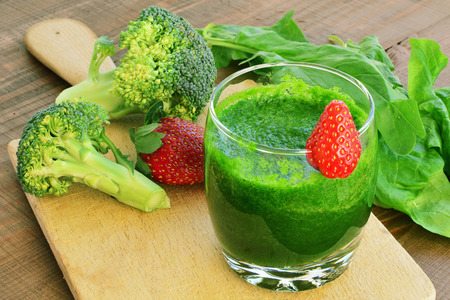 Green vegetable smoothie with strawberries. Spinach, broccoli, cucumber smoothie in glass.