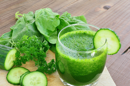 Green vegetable juice. Spinach, broccoli, cucumber, parsley smoothie in glass on wooden table.