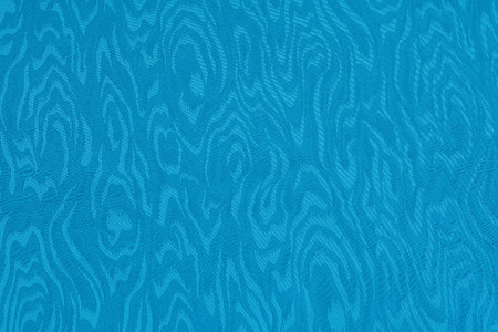 Blue cyan silk damask fabric with moire pattern. Wavy textured background.