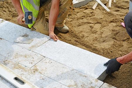 Worker tippen Fertiger in Stelle mit Gummihammer. Installation von Granit Pflasterblöcke Serie mit Bewegungsunschärfe auf Hämmer und Händen. Standard-Bild - 40334358