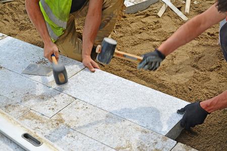 Werknemers tikken straatstenen op zijn plaats met rubberen hamers. Installatie van granieten bestrating blokken serie met motion blur op de hamers en handen.