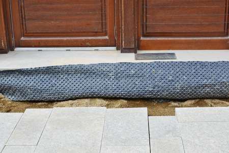 impermeable: Waterproofing membrane to protect foundations and flooring. Installation of granite paver blocks series. Stock Photo