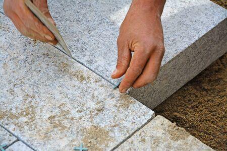 Schließen Fügen, Montage von Granit Pflasterblöcke Serie. Arbeiter schafft eine enge Verbindung zwischen Pflasterblöcke für Fugenmaterial mit Abstandhalter aus Kunststoff. Standard-Bild - 40334366