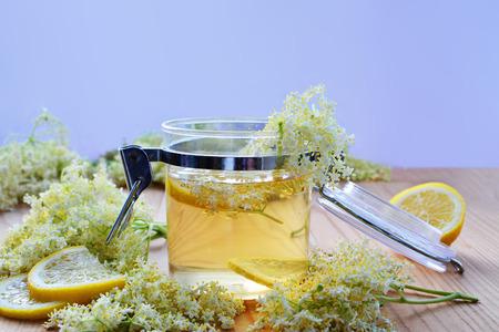diuretic: Elderflower syrup in transparent jar with fresh elderflower blossoms and lemon. Stock Photo