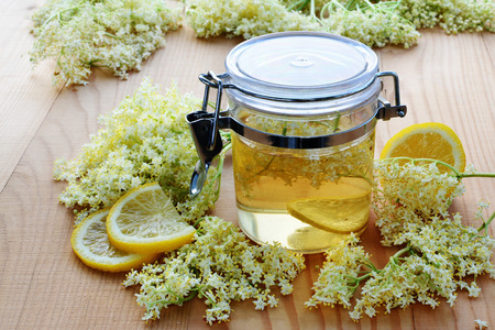 Elderflower syrup in transparent jar with fresh elderflower blossoms and lemon. Stockfoto