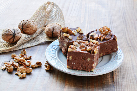 fudge: Homemade chocolate fudge with walnuts on plate over wooden table.