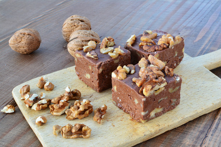 Homemade chocolate fudge with walnuts on plate over wooden table.