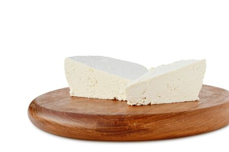 whey: Ricotta, fresh whey cheese pieces on wooden board over white background. Stock Photo