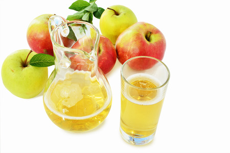 Hard Apple Cider in glass and pitcher with ripe apples over white background. Standard-Bild