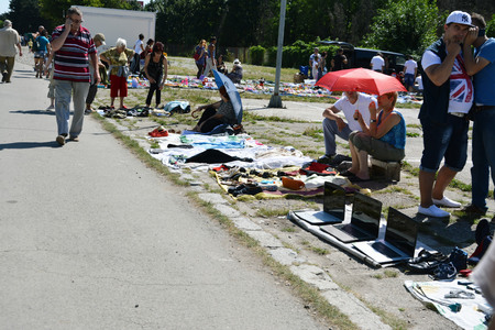 used clothes: CLUJ-NAPOCA, ROMANIA - AUGUST 02, 2015: Vendors selling secondhand clothes and used goods at a flea market.