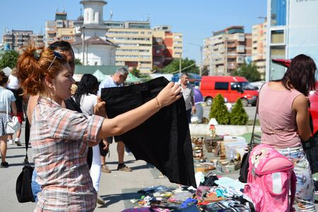 secondhand: CLUJ-NAPOCA, ROMANIA - AUGUST 02, 2015: Woman shopping clothes at a flea market. Secondhand clothes stall and used goods booth. Editorial