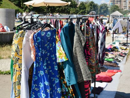 secondhand: CLUJ-NAPOCA, ROMANIA - AUGUST 02, 2015: Clothes on a rack in a flea market. Secondhand clothes stall and used goods booth.
