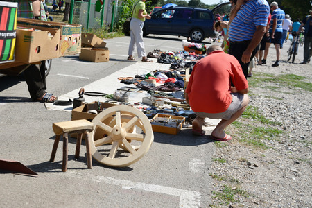 used clothes: CLUJ-NAPOCA, ROMANIA - AUGUST 02, 2015: People shopping secondhand clothes and used household goods at a flea market.