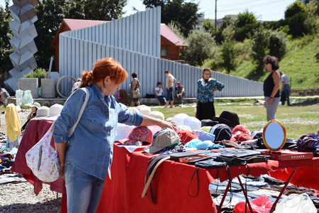 used clothes: CLUJ-NAPOCA, ROMANIA - AUGUST 02, 2015: Woman shopping  hats and caps at a flea market. Secondhand clothes stall and used goods.