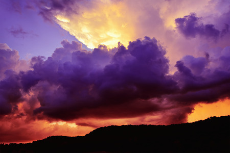 cloud formations: Dramatic dark purple and red storm clouds billow around a bright gap through which light rays stream.