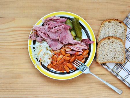 hock: Beans with meaty ham hock cut off, pickles and coleslaw on plate. Stock Photo